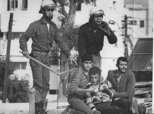 ממה אנחנו מפחדים?  זוהי התמונה (ארכיון ידיעות אחרונות) שחונקת אותי בכול פעם שאני מביט בה, שמעון ירוי, כנראה כבר לא בין החיים על גג הבית, נאחד בידי אחיו הצעיר משמאל, ועוד תושב השכונה כנראה — בעוד שני שוטרים עומדים מעליו, לא מרפים מהאלות, צורחים כנראה/אני מקווה לעזרה….ישראל 1982!
