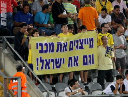 Maccabi Tel Aviv fans are holding a sign stating: 'Representing Maccabi and Israel'