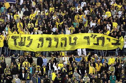 Beitar fans hold a banner stating 'Beitar Pure forever' and in